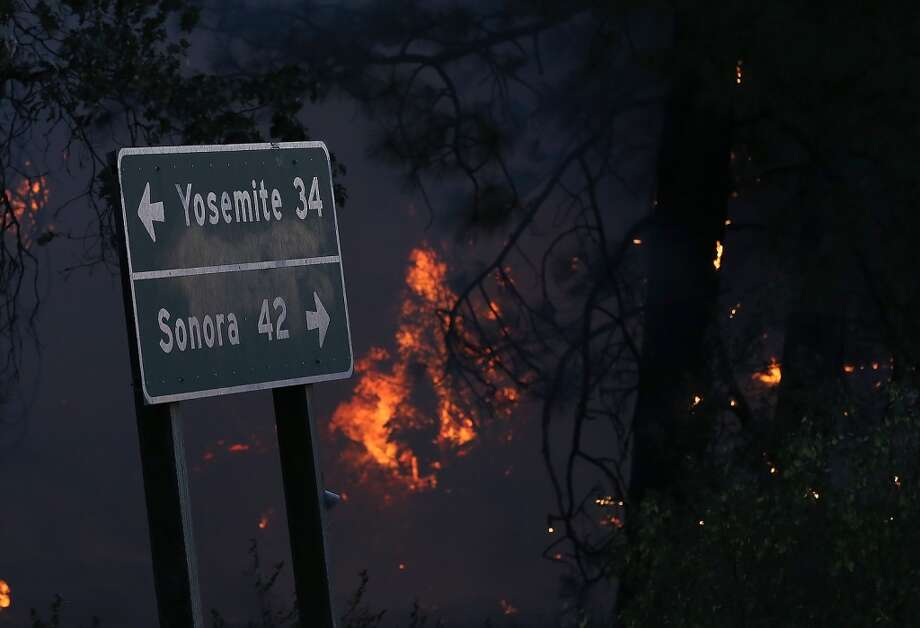Flames from the Rim Fire burn near a road sign pointing towards Yosemite on August 21, 2013 in Groveland, California. The Rim Fire continues to burn out of control and threatens 2,500 homes outside of Yosemite National Park. Photo: Getty Images