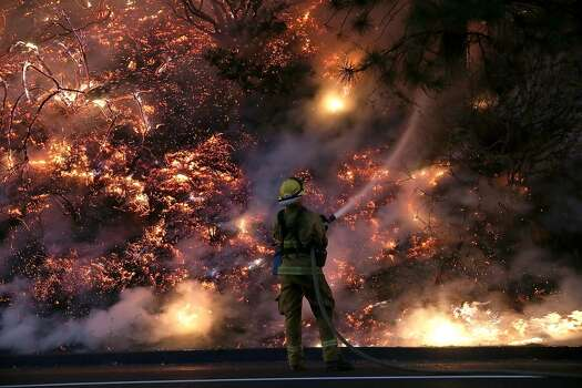A firefighter uses a hose to douse the flames of the Rim Fire on August 24, 2013 near Groveland, California. The Rim Fire continues to burn out of control and threatens 4,500 homes outside of Yosemite National Park. Photo: Getty Images