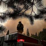 A member of the West Stanislaus County Fire Department monitors the Rim Fire along highway 120 on August 24, 2013 near Groveland, California. The Rim Fire continues to burn out of control and threatens 4,500 homes outside of Yosemite National Park.