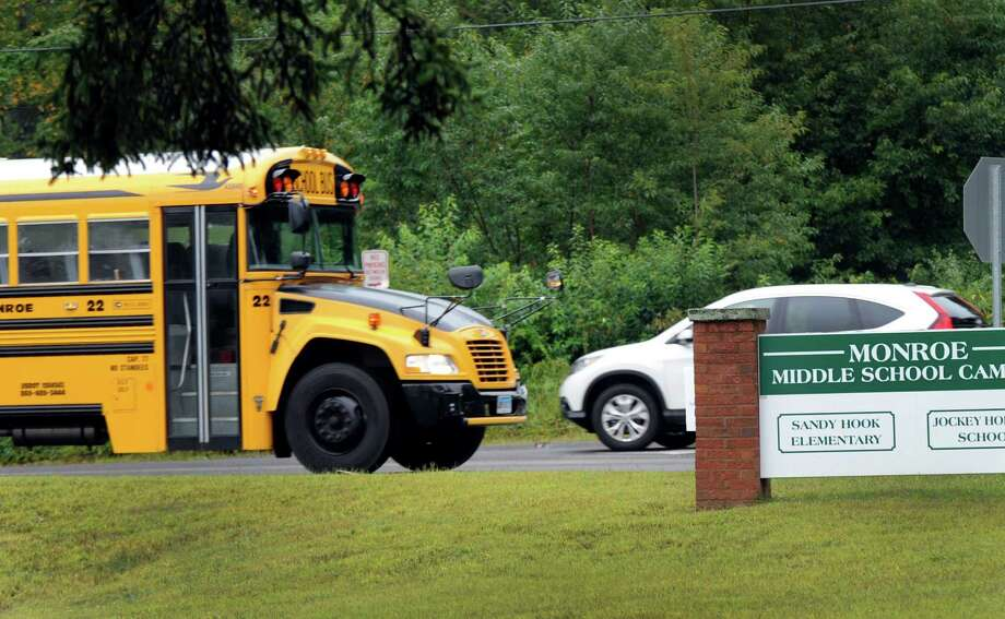 A bus leaves the entrance the Sandy Hook Elementary School in Monroe, Conn. Tuesday morning. School opened in Newtown for students, Tuesday, Aug. 27, 2013. Photo: Carol Kaliff / The News-Times