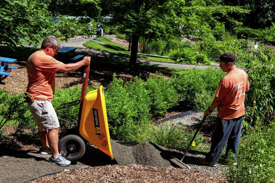 Scott Crane and Ben Maini, Reynolds & Rowella, LLP partners, work on the grounds of Tarrywile Park, a 722-acre estate in Danbury, as part of Day of Caring. Photo: Contributed