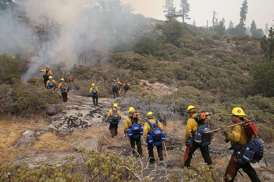 Firefighters move in to douse a spot fire while battling the Rim Fire on August 24, 2013 in Yosemite National Park, California. The Rim Fire continues to burn out of control and threatens 4,500 homes outside of Yosemite National Park. Photo: Justin Sullivan, Getty Images