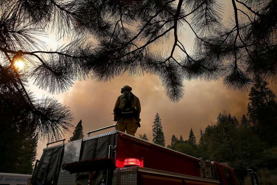 A member of the West Stanislaus County Fire Department monitors the Rim Fire along highway 120 on August 24, 2013 near Groveland, California. The Rim Fire continues to burn out of control and threatens 4,500 homes outside of Yosemite National Park. Photo: Justin Sullivan, Getty Images