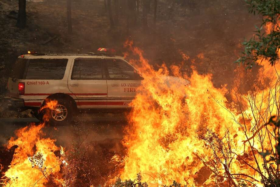 A vehicle from San Andreas fire department drives by a back fire as crews battle the Rim Fire on August 21, 2013 in Groveland, California. The Rim Fire continues to burn out of control and threatens 2,500 homes outside of Yosemite National Park. Photo: Justin Sullivan, Getty Images