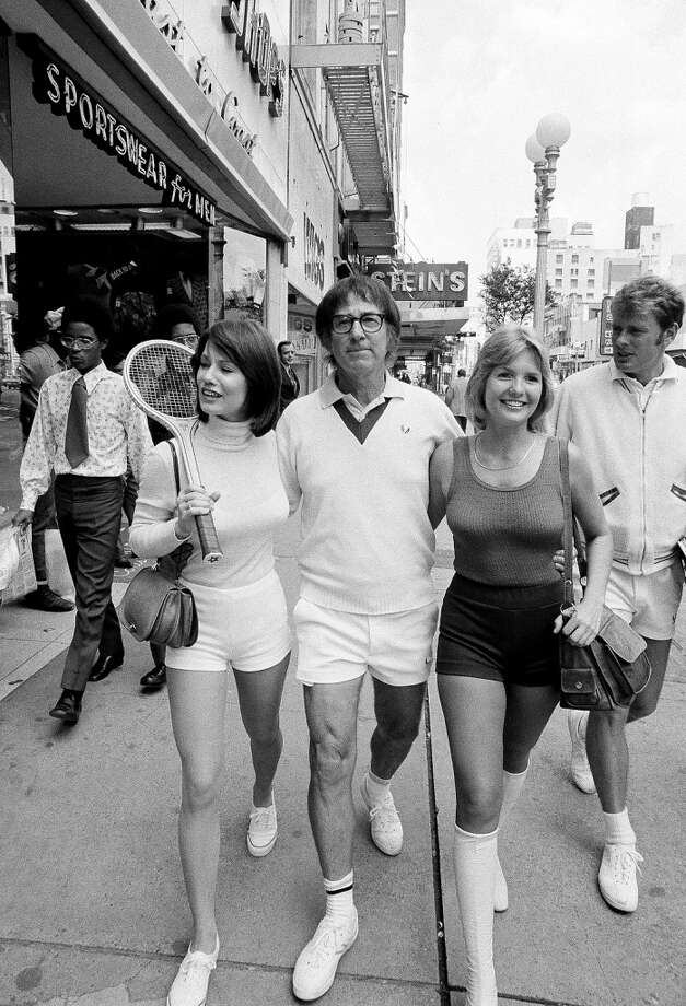 "Bobby Riggs strolls down Houston's main street, Sept. 13, 1973, with two of his ""Bosom Buddies,"" members of a group of girls that will be cheering Riggs to victory in his upcoming match against Billie Jean King in the Astrodome.  The ""Buddies"" are unidentified. Photo: Ed Kolenovsky, ASSOCIATED PRESS"