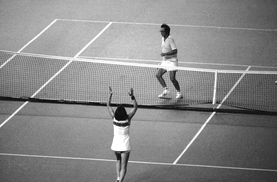 Mrs. Billie Jean King raises her hands in triumph as her Opponent, Bobby Riggs, prepares to hurdle the net following her straight-set victory over him in tennis match at the Houston Astrodome in Houston on Sept. 20, 1973. Photo: Anonymous, AP
