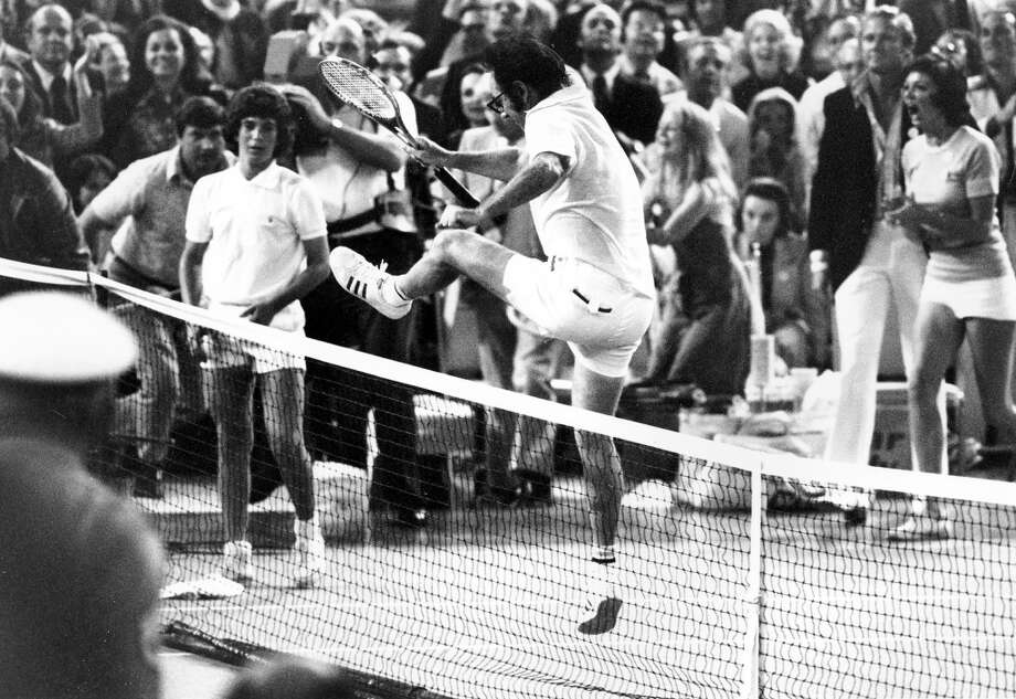 Bobby Riggs leaps over the net to congratulate Billie Jean King after she beat him in straight sets in the Houston Astrodome, Texas, on Sept. 20, 1973.  King won 6-4, 6-3, 6-3. Photo: ASSOCIATED PRESS