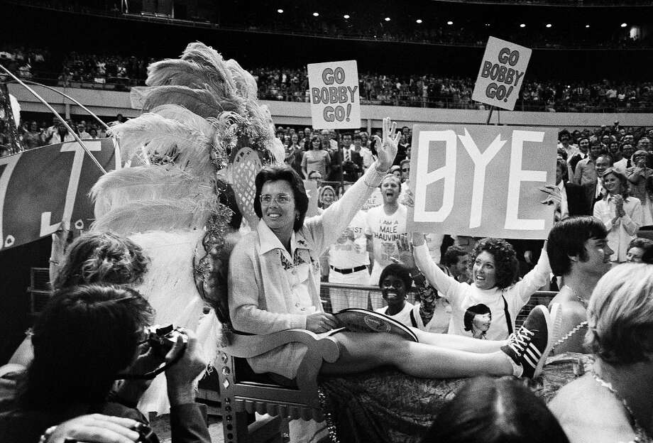 Billie Jean King waves to crowds at the Astrodome in Houston on Sept. 20,1973 as she is borne onto the crowd on a multi-colored throne carried by four men for her match with Bobby Riggs. Photo: Anonymous, AP