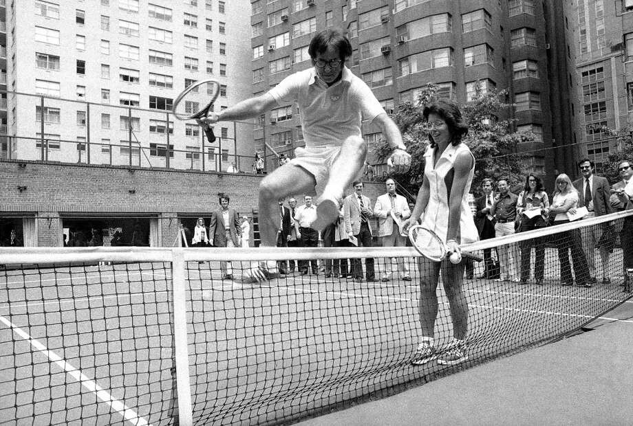 Wimbledon Champ Billie Jean King holds down the net as Bobby Riggs, the 55-year-old tennis player who bested Margaret Court in a grudge match, jumps over the net in New York on July 11, 1973. King and Riggs announced that they will meet in similar $100,000 tennis match at a time and place as yet unannounced. Photo: Anonymous, AP