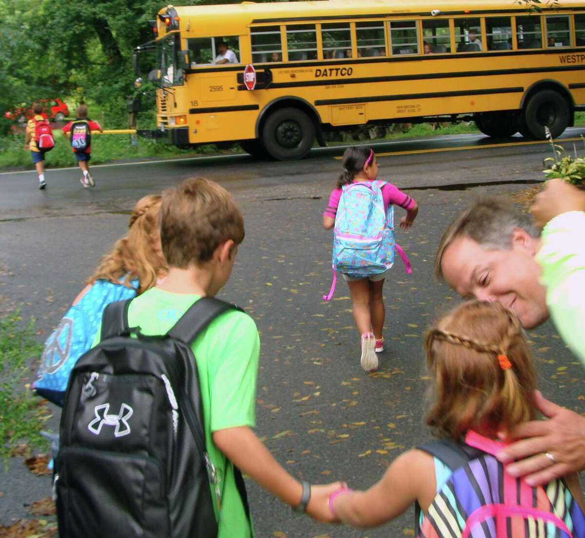 Westport August 27 Carter Gay, 8, left, a third-grader at Long Lots Elementary School, holds the hand of his younger sister Reese, 4, as their father, Willis, bends down to kiss his daughter and wish her well at her first day of Kindergarten Tuesday.