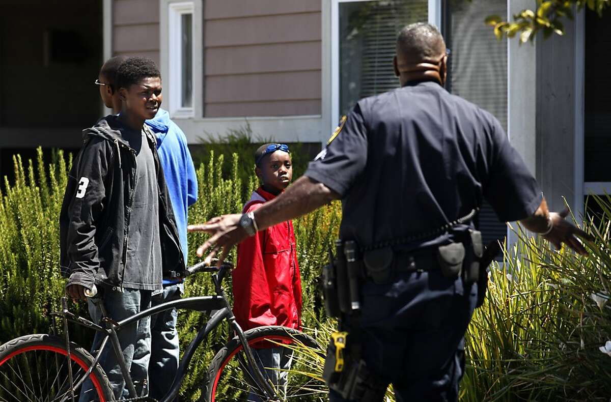 Oakland Police Officers talk with neighborhood kids as they arrest a suspect with a Federal Warrant, Friday July 26, 2013, in Oakland, CAlif.