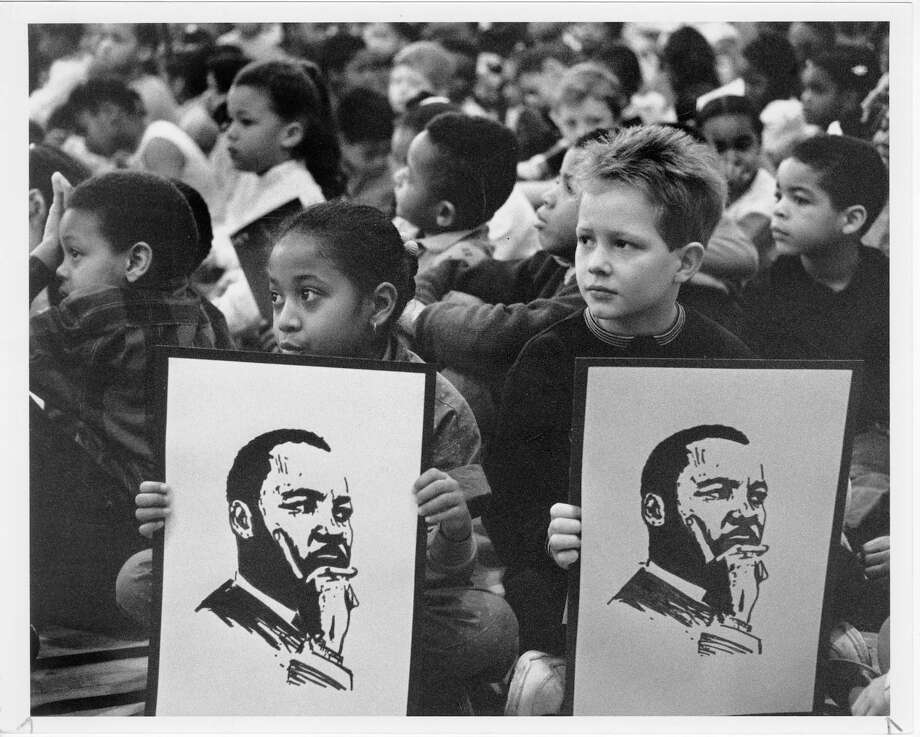 Tanya Johnson, 9, and Kyle Bauer, 8, third graders at TT Minor elementary school in Seattle, hold posters of Dr. Martin Luther King during a program in King's honor at the school. Mayor Norm Rice addressed the students on January 11, 1990. Photo: Kurt Smith/Copyright MOHAI, Seattle Post-Intelligencer Collection, 2000.107_print_KingMartinLutherSeattle_004 Photo: Kurt Smith, Copyright MOHAI, Seattle Post-Intelligencer Collection / Copyright Museum of History & Industry