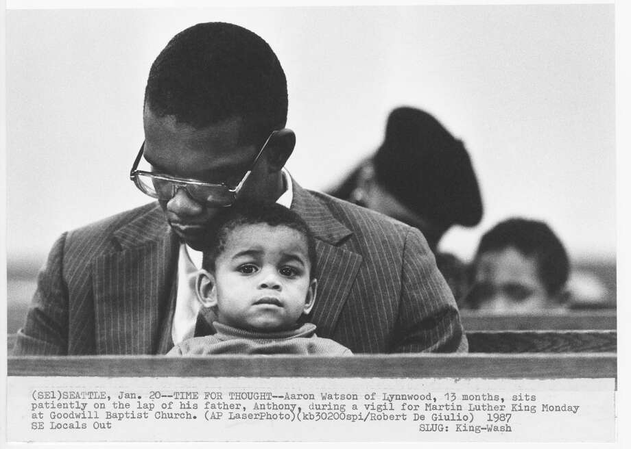 Aaron Watson of Lynnwood, 13 months, sits patiently on the lap of his father, Anthony, during a vigil for Martin Luther King, Jr.on January 20, 1987 at Goodwill Baptist Church. Photo: Robert De Giulio/Copyright MOHAI, Seattle Post-Intelligencer Collection, 2000.107_print_KingMartinLutherSeattle_002 Photo: Robert De Giulio, Copyright MOHAI, Seattle Post-Intelligencer Collection / Copyright Museum of History & Industry