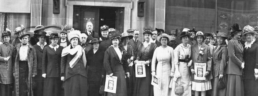Suffragists in Seattle holding copies of the
