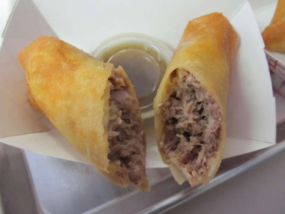 Deep Fried Cuban Roll - A filling of slow-cooked pork shoulder, chopped ham, Swiss cheese, pickles and secret sauce is spread onto a slice of Swiss cheese, rolled up in pastry dough and deep fried. Roll is served with a side of majo sauce for dipping. (Credit State Fair of Texas)