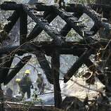 Firefighters douse hot spots amid the smoldering ruins of the Berkeley Tuolumne Camp near Groveland, California, Monday, August 26, 2013. The 1922 village of cabins and a large dining hall on the Tuolumne River that once served 4000 people annually was almost totally destroyed by the massive, uncontrolled Rim Fire. All guests had been evacuated. (Don Bartletti/Los Angeles Times/MCT)