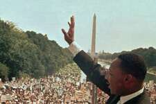 """Dr. Martin Luther King Jr. acknowledges the crowd at the Lincoln Memorial for his """"I Have a Dream"""" speech during the March on Washington, D.C. Aug. 28, 1963. The Washington Monument is in background."""