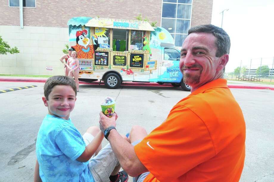 Thomas Dunn shares a treat with son Owen, 10, from their Kona shaved ice truck as Kathy Mabry and her great-niece Emma Harms, 8, choose a flavor for their treat at Quillian Center. Thomas Dunn says he loves running the truck and working with his son. Photo: Â Tony Bullard 2013, Freelance Photographer / © Tony Bullard & the Houston Chronicle