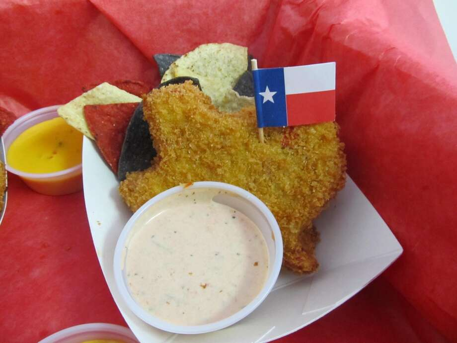 "Fernie's Deep Fried King Ranch Casserole–This Texas-shaped creation is melted cheese, salty, spicy, goodness that is dipped in a zesty southwestern egg wash and coated in panko bread crumbs.  Deep fried golden brown and crunchy on the outside; steamy and creamy on the inside! Served with a side of red, white and blue tortilla chips and your choice of our homemade ""salsafied"" sour cream or cheesy queso. (Credit State Fair of Texas)"