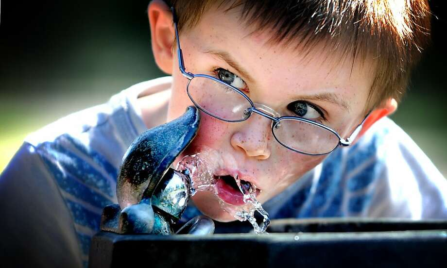 From one squirt to another:Four-year-old Lance Anderson gets a drink and a face wash from a 