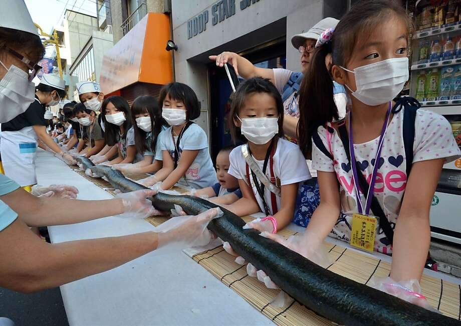 Hundreds of masked children help assemble a 393-foot-long sushi roll to be served at a summer festival in Tokyo. Photo: Yoshikazu Tsuno, AFP/Getty Images