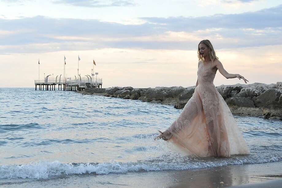 Low tide, high fashion: Italian model Eva Riccobono tests how her lace gown handles saltwater at Excelsior beach on 