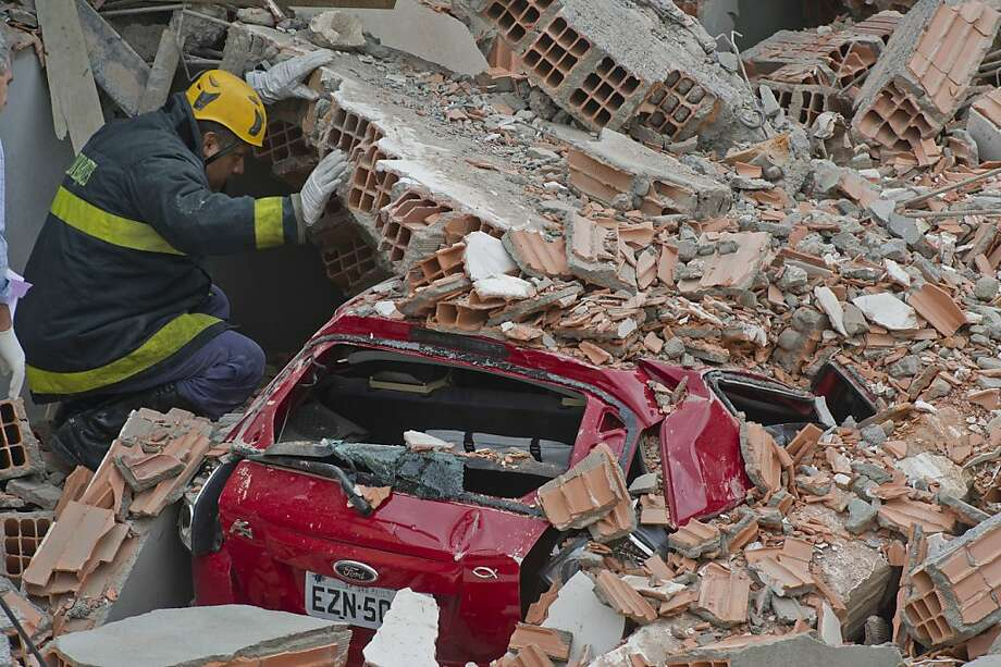 Rescuers search for survivors in the rubble of a building under construction that 