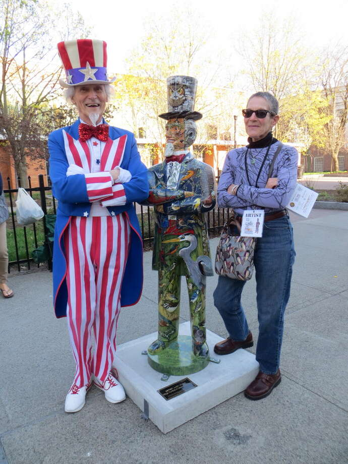 "Judith Vincent of Troy and her Uncle Sam creation stand with Fred Polnisch at the statue depicting the Birds Of Oakwood Cemetery (83 birds) where Samuel Wilson, the inspiration behind Uncle Sam, is buried. On the back are many more birds, the crematorium and Wilson's gravestone.  (Craig Bartholomew) ""Doing this statue of Uncle Sam was a challenge that brought me great satisfaction,"" said Vincent, who said she spent about 200 hours of work on it. ""My statue is at Barker Park which was originally a cemetery where Samuel Wilson's very young children were buried and then moved to Oakwood Cemetery when it was decided to erect Troy's first city hall at this location."""