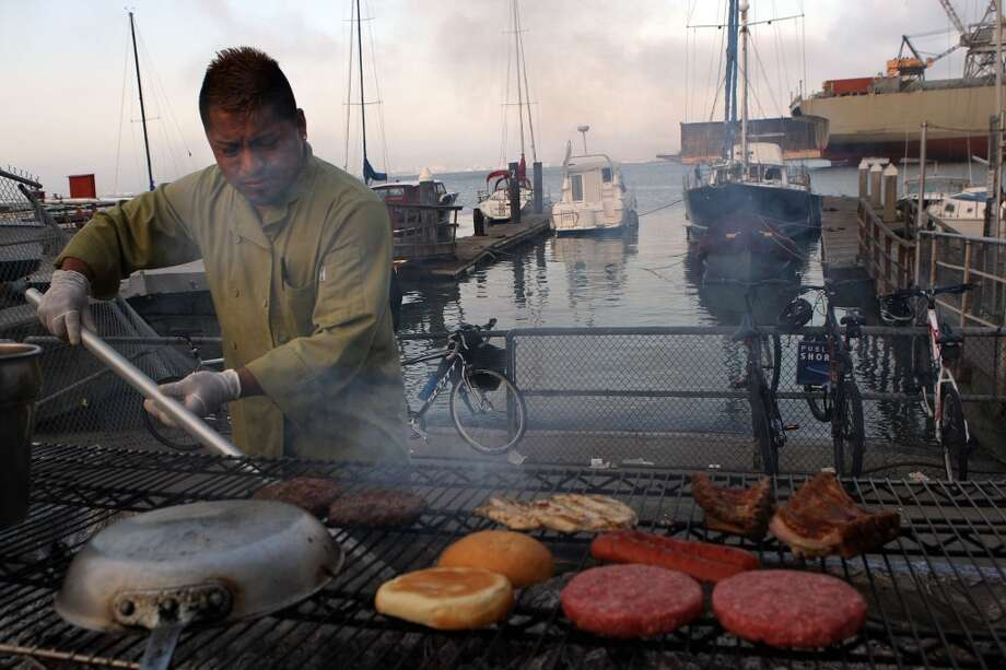 Eduardo Hernandez works the barbecue at the Ramp in San Francisco. Photo: Liz Hafalia, The Chronicle