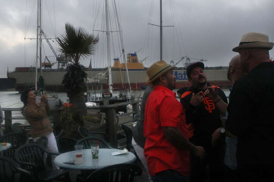 Bine Arceo  (orange shirt) and Carlos Plandino (right ) meet with friends at the Ramp. Photo: Liz Hafalia, The Chronicle