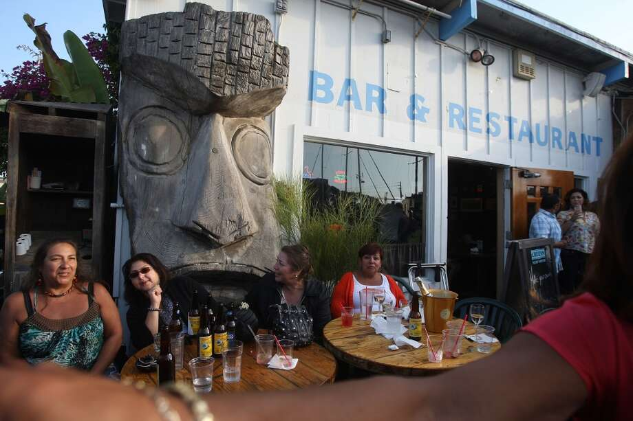 Friends and family celebrate Feliciano Chavez' birthday in front of a wooden tiki god at the Ramp. Photo: Liz Hafalia, The Chronicle
