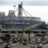 Bay area communters approach the toll booths of the Bay Bridge as the old Cantilever section towers over the old span rear Wednesday November 23, 2011. No sooner did Cal-Trans say Happy 75th? birthday, Bay Bridge. Now their almost ready to say get lost. Even as the bridge's Nov. 12th birthday was celebrated with speeches, a parade of antique cars and a birthday cake on Treasure Island, Caltrans officials were plotting the demise of its eastern half. With construction of the $6.3 billion? new east span finally progressing -- and the opening set for 2013?-- the demolition of the current east span is in the design stage, with preparations being made to start tearing the old gray lady to pieces soon after the ribbon is cut for the new span.