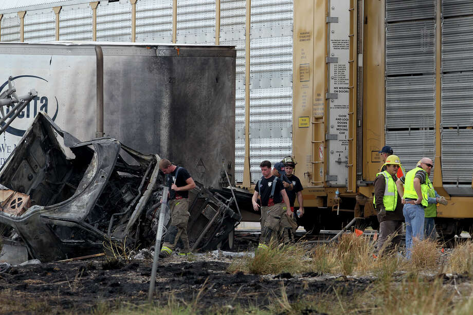 San Antonio firefighters and Union Pacific workers inspect the location where a tractor trailer rig collided with a northbound Union Pacific freight train just north of Walzem Road on the IH-35 access road Tuesday August 27, 2013. San Antonio Fire Chief Charles Hood said the accident took place shortly before 1:00 p.m. and the truck's driver and the train crew were not injured. The truck was carrying matresses. Photo: JOHN DAVENPORT, SAN ANTONIO EXPRESS-NEWS / ©San Antonio Express-News/Photo may be sold to the public