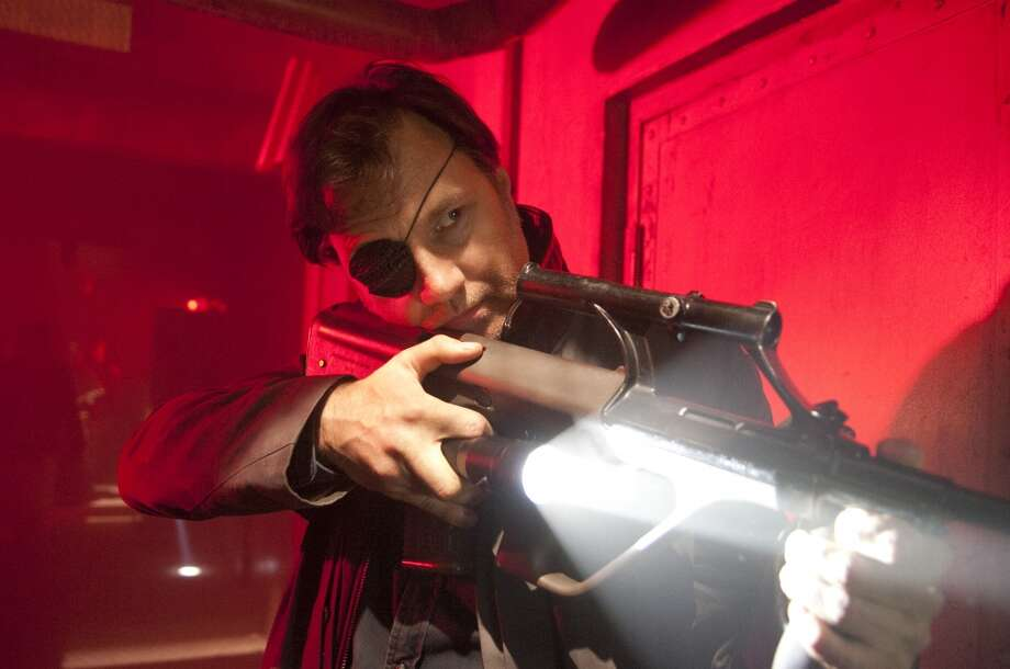 The one-eyed Governor (David Morrissey) gives Milton (Dallas Roberts) a knife and orders him to kill Andrea (Laurie Holden). Milton refuses so the Governor, already upset about Milton burning the pit walkers, turns the knife on him. Photo: Gene Page/AMC