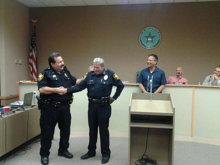 Hollywood Park Deputy Police Chief Joe Quintero, left, congratulates retiring Police Chief Steve Kwiecien, center, at the Aug. 20 City Council meeting. At right is Mayor David Ortega.