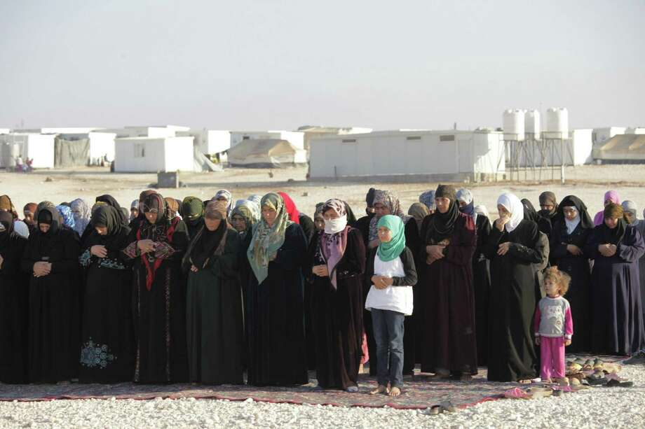 Syrian refugee women pray  at a refugee camp in Jordan. The Syrian humanitarian crisis demands international assistance. Photo: Mohammad Hannon / Associated Press