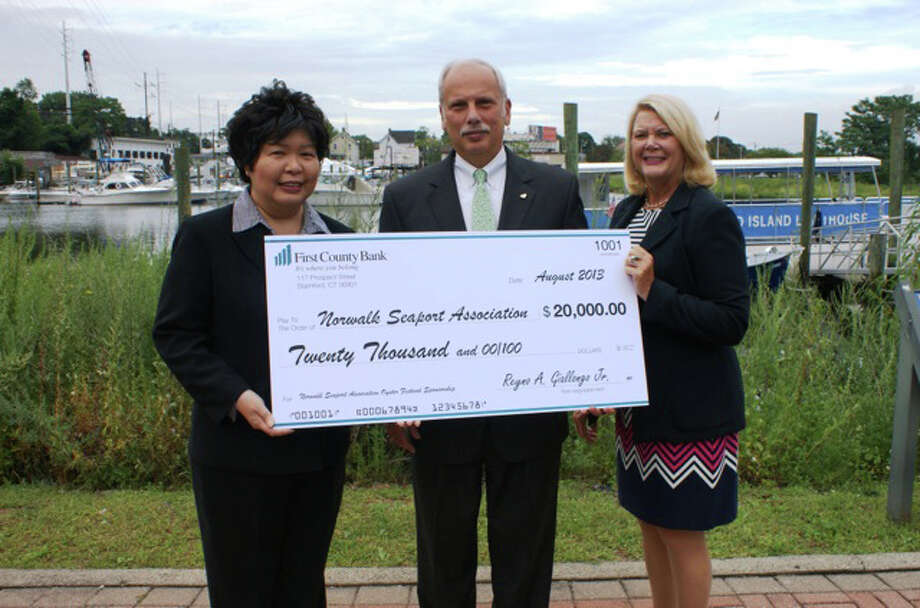 Reyno Giallongo, chairman and CEO of First County Bank, and Katherine Harris, president and COO First County Bank, present a $20,000 check to Irene Dixon, president of the Norwalk Seaport Association. First County Bank will sponsor Norwalk's Sept. Oyster Festival. Photo: Contributed Photo