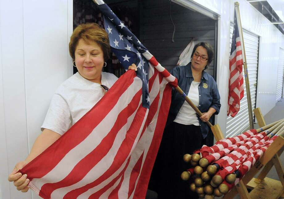 Kngwood Rotary Club members Carolyn Wise left, and Tommie Buscemi examine the condition of the U.S. flags inside a storage unit. During certain patriotic holidays The Rotary Club places the flags at the homes of residents and at businesses that have subscribed to the service. Photo: David Hopper, Freelance / freelance