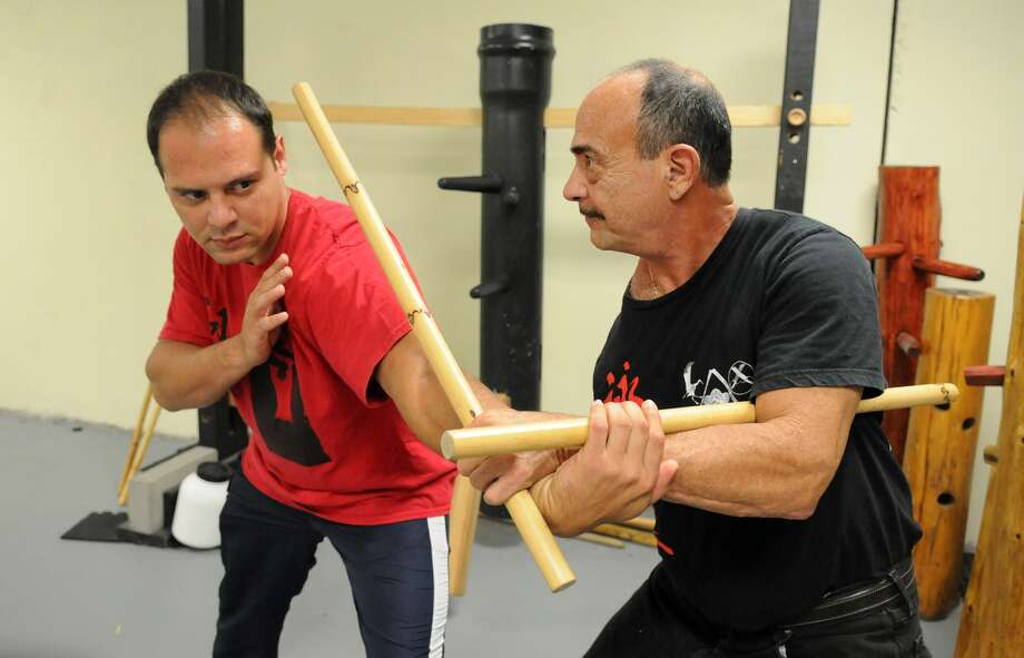 The Woodlands resident Ramon Diaz, right, demonstrates a move with his son, Charlie Diaz, at the Iron Sports Gym they own in Spring. Ramon, who has one arm, is a master of several martial art forms. He teaches his students to persevere despite challenges. Photo: Jerry Baker, Freelance
