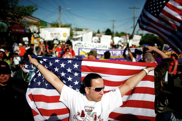 Hector Solano of El Salvador holds the U.S. flag as he marches in the annual May Day march and rally in downtown Seattle on Friday May 1, 2009. Marchers called for immigration reform and worker rights.  (Photo by Joshua Trujillo/Seattlepi.com).