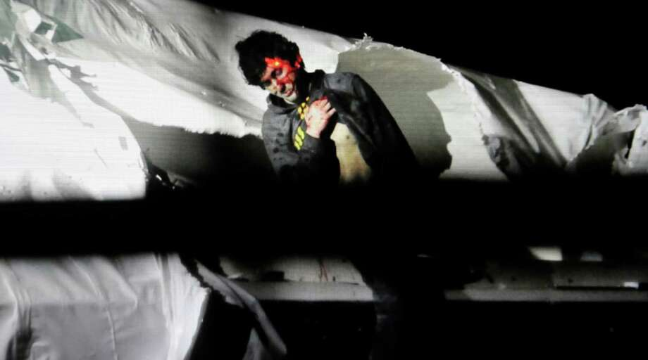 In this Friday, April 19, 2013 Massachusetts State Police photo, 19-year-old Boston Marathon bombing suspect Dzhokhar Tsarnaev leans over in a boat at the time of his capture by law enforcement authorities in Watertown, Mass.  Court documents released Monday, Aug. 19, 2013 describe the extent of injuries to Tsarnaev, including multiple gunshot wounds to his face and a skull fracture. Photo: Sean Murphy, Associated Press / Massachusetts State Police