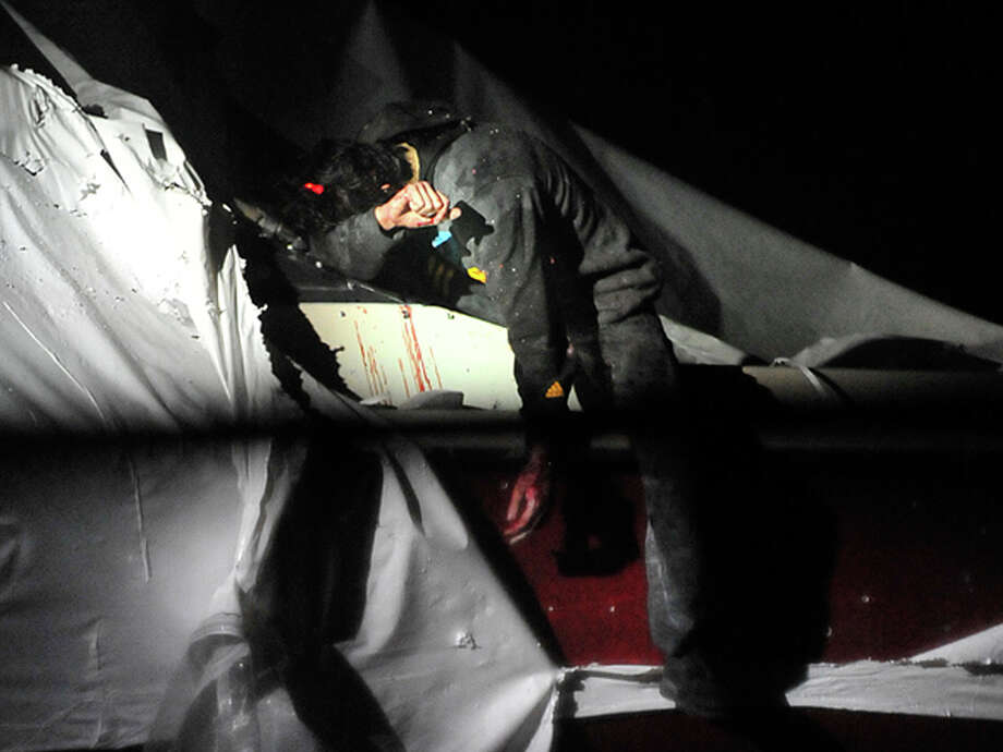In this Friday, April 19, 2013 photo provided by the Massachusetts State Police, Boston Marathon bombing suspect Dzhokhar Tsarnaev leans over in a boat at the time of his capture by law enforcement authorities in Watertown, Mass. Photos of the Boston Marathon bombing suspect's surrender have been posted on the Boston Magazine website. The additional images, made public Tuesday, Aug. 27, 2013, were among those released to the magazine last month by a state police photographer. Photo: Sean Murphy, Associated Press / Massachusetts State Police