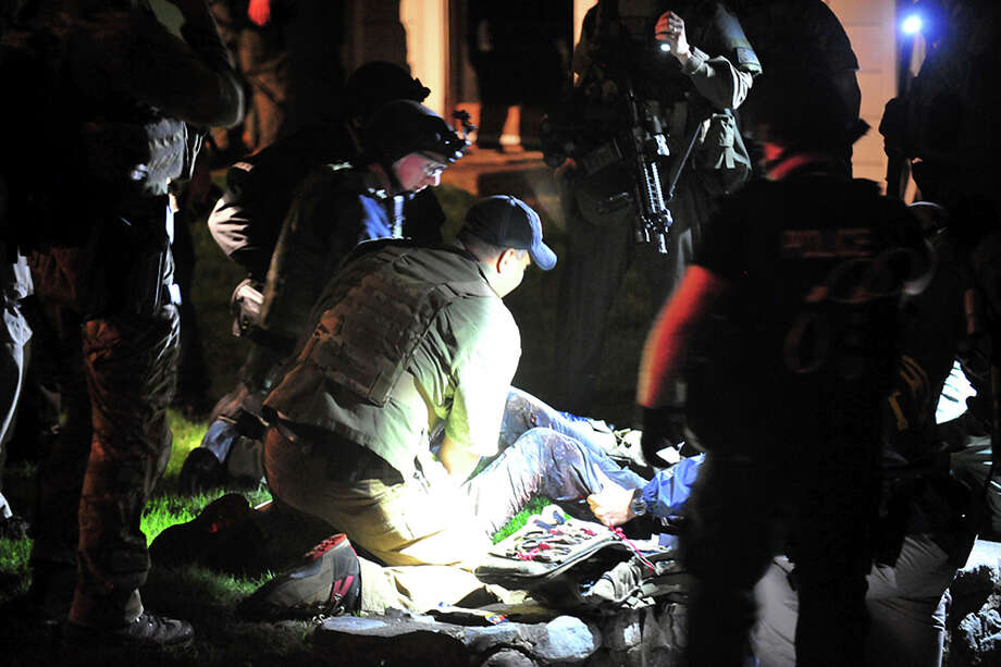In this Friday, April 19, 2013 Massachusetts State Police photo, tactical emergency medical technicians tend to Boston Marathon bombing suspect Dzhokhar Tsarnaev, partially obscured center, at the time of his capture by law enforcement authorities in Watertown, Mass. Photos of the Boston Marathon bombing suspect's surrender have been posted on the Boston Magazine website. The additional images, made public Tuesday, Aug. 27, 2013 were among those released to the magazine last month by a state police photographer. Photo: Sean Murphy, Associated Press / Massachusetts State Police