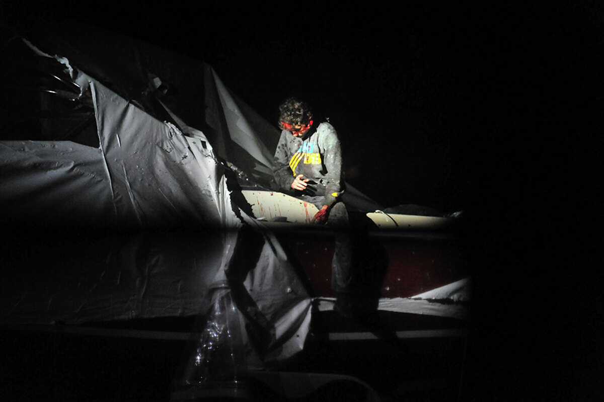 In this Friday, April 19, 2013 photo provided by the Massachusetts State Police, Boston Marathon bombing suspect Dzhokhar Tsarnaev leans over in a boat at the time of his capture by law enforcement authorities in Watertown, Mass. Photos of the Boston Marathon bombing suspect's surrender have been posted on the Boston Magazine website. The additional images, made public Tuesday, Aug. 27, 2013, were among those released to the magazine last month by a state police photographer.