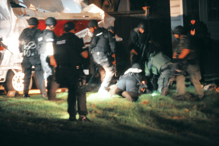 In this Friday, April 19, 2013 photo provided by the Massachusetts State Police, law enforcement officials apprehend Boston Marathon bombing suspect Dzhokhar Tsarnaev at the time of his capture in Watertown, Mass. Photos of the Boston Marathon bombing suspect's surrender have been posted on the Boston Magazine website. The additional images, made public Tuesday, Aug. 27, 2013 were among those released to the magazine last month by a state police photographer. Photo: Sean Murphy, Associated Press / Massachusetts State Police
