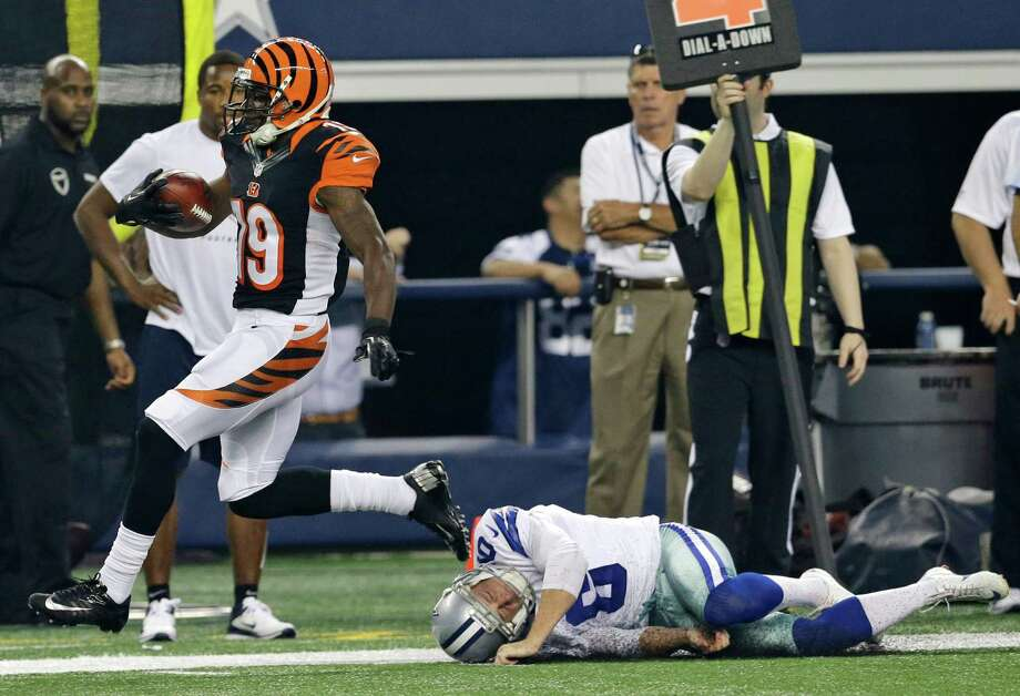 Cowboys punter Chris Jones, right, had a rough sequence against the Bengals, hitting the video board with one punt, then coming up empty on an attempted tackle during Brandon Tate's touchdown return on the re-kick. Photo: LM Otero, STF / AP