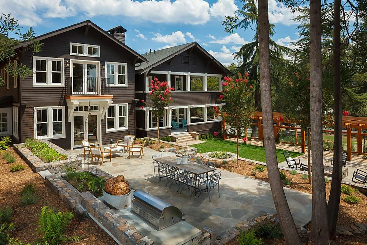 The backyard includes a stone patio, grass pad, fire pit and built-in barbecue.
