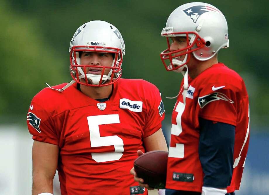 New England Patriots football quarterbacks  Tim Tebow (5) and Tom Brady stand together during team practice in Foxborough, Mass., Monday, Aug. 26, 2013. (AP Photo/Elise Amendola) ORG XMIT: MAEA103 Photo: Elise Amendola / AP