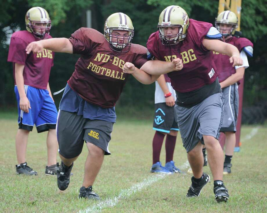 Offensive line players Zach Bell of Saratoga Central Catholic, left, and Zach Burt of Bishop Gibbons work on a drill during Bishop Gibbons/Saratoga Central Catholic football practice at Bishop Gibbons High School on Monday, Aug. 26, 2013 in Schenectady, N.Y. This is one of two teams in 2013 to have a combined roster. (Lori Van Buren / Times Union) Photo: Lori Van Buren / 00023635A