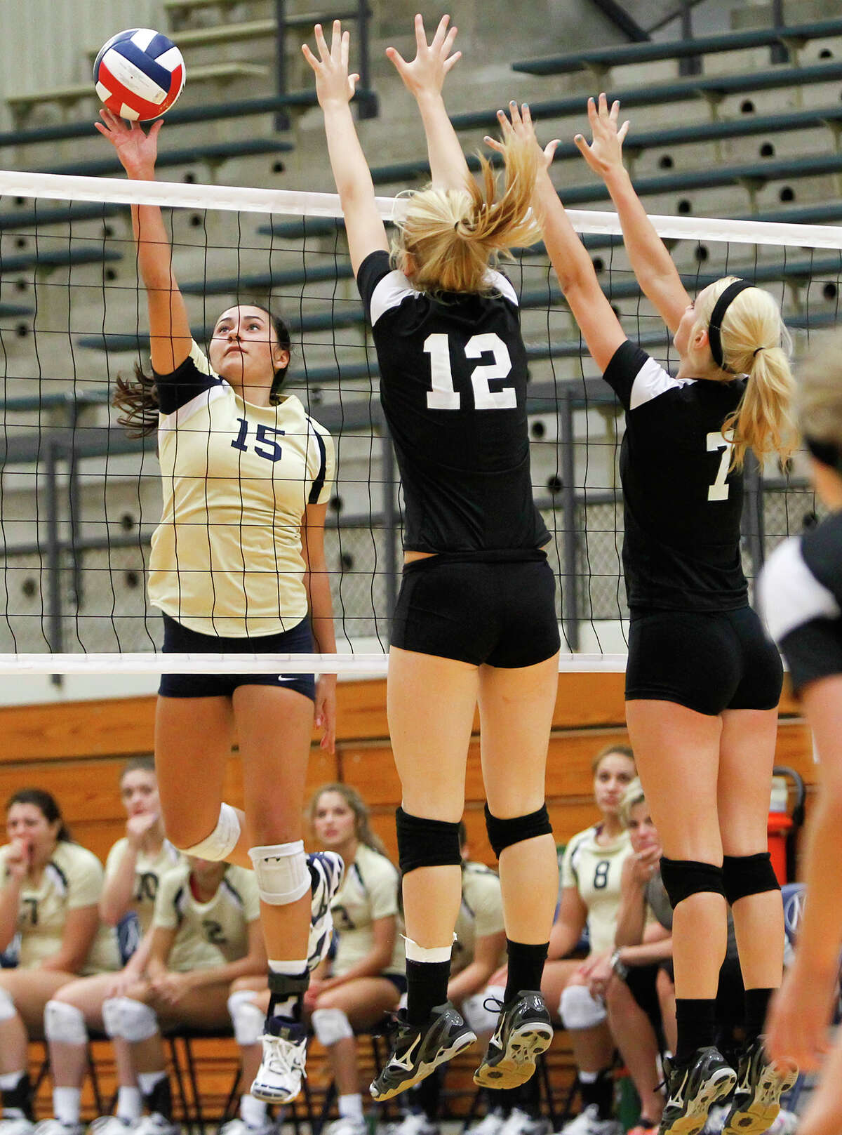 O'Connor's Brianna Sotello (left) leaps to put a shot past Clark's Kim Gillette (center) and Kristin Moczygemba during their District 27-5A volleyball match at Paul Taylor Field House on Tuesday, Aug. 27, 2013. O